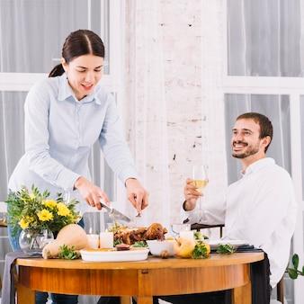 Frau, die gebackenes huhn am festlichen tisch schneidet