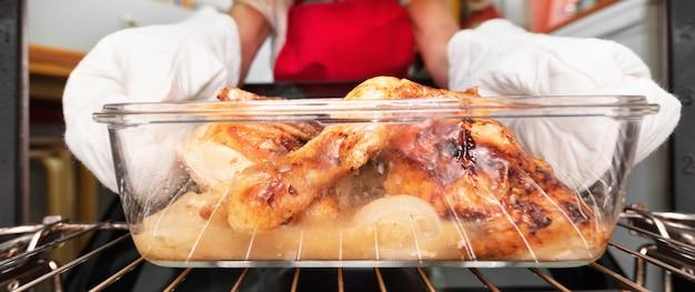 Frau, die gebratenes huhn vom ofen nimmt. im ofen kochen.