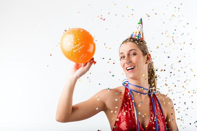 Frau, die geburtstag an einer dusche von konfettis mit ballon feiert