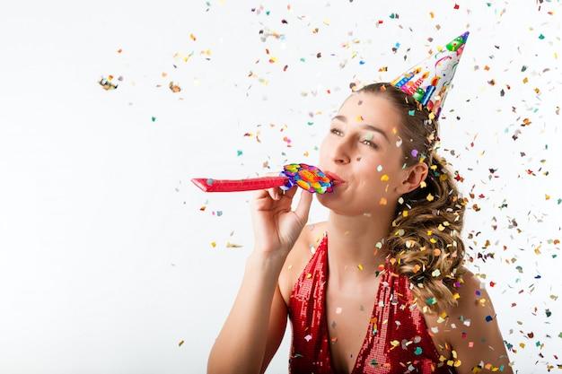 Frau, die geburtstag mit ausläufer und partyhut feiert