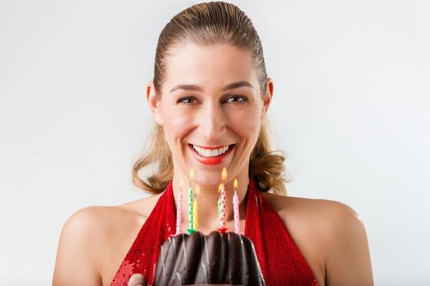 Frau, die geburtstag mit kuchen und kerzen feiert