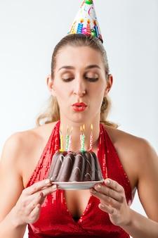 Frau, die geburtstag mit schlagkerzen des kuchens heraus feiert