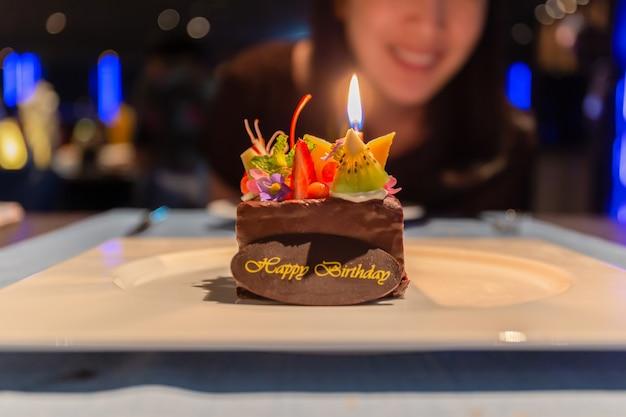 Frau, die geburtstag mit schokoladenfruchtkuchen mit kerzenlicht feiert Premium Fotos