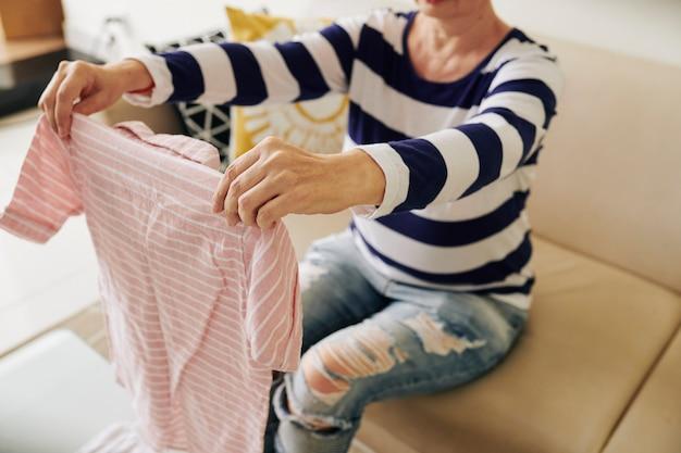 Frau, die gefaltetes gestreiftes hemd hält