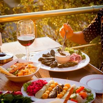 Frau, die gefüllte weinblätter mit verschiedenen arten von salaten und einem glas wein auf einem tisch mit bäumen auf hintergrund isst. high angle view.