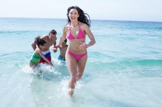 Frau, die gegen familie am strand läuft