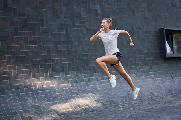 Frau, die gegen schwarze wandoberfläche springt und läuft