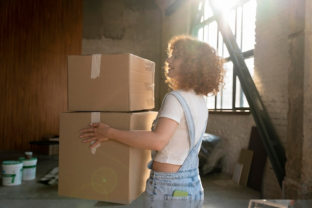 Frau, die gegenstände in kartons für den einzug in ein neues haus handhabt