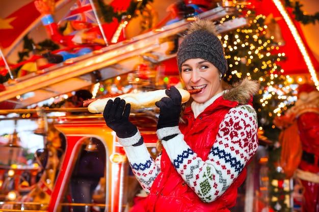 Frau, die gegrillte wurst auf weihnachtsmarkt isst