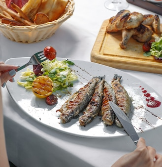 Frau, die gegrillten fisch mit kopfsalat, gegrillter zitrone und tomate isst
