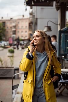 Frau, die geht und ein smartphone in der straße benutzt