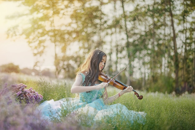 Frau, die geige im naturblumenfeld spielt
