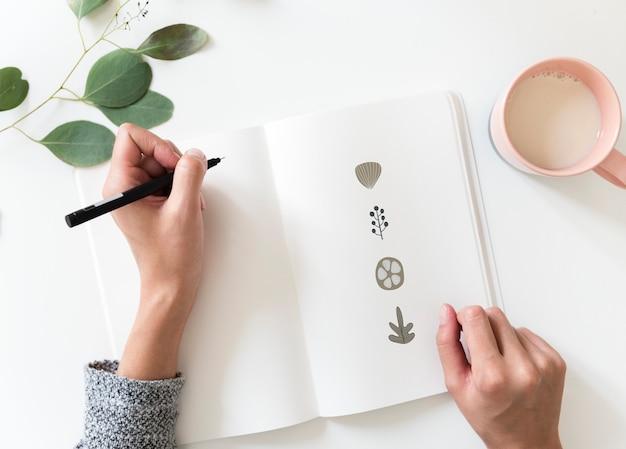 Frau, die gekritzelelemente in einem notizbuch zeichnet