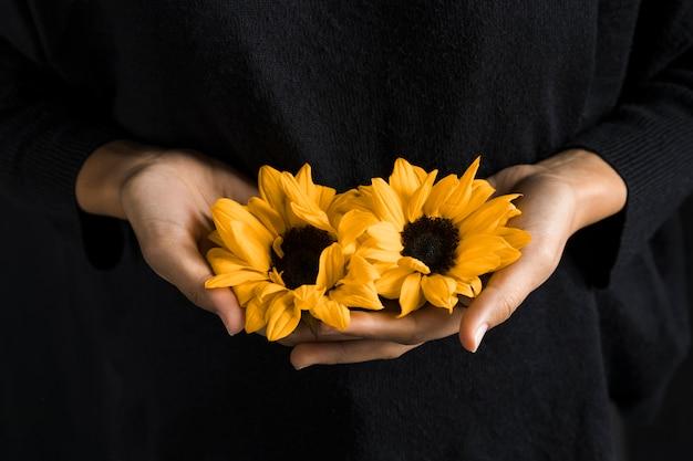Frau, die gelbe blumen in den händen anhält