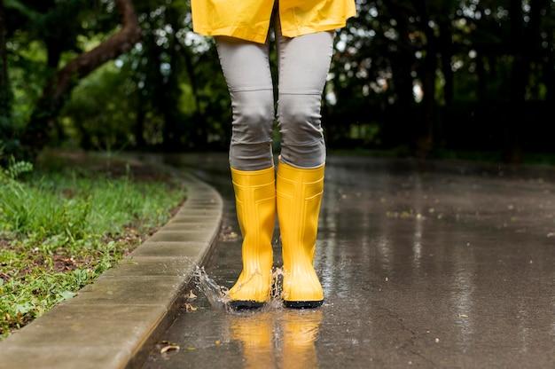 Frau, die gelbe regenstiefel trägt
