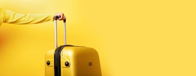 Frau, die gelben koffer in der hand über gelb hält