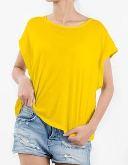 Frau, die gelbes t-shirt und kurze rissjeans auf weiß trägt