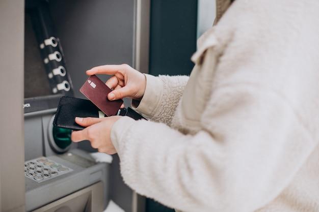 Frau, die geld am geldautomaten außerhalb der straße abhebt