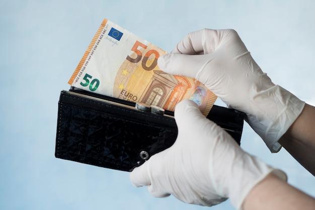 Frau, die geld aus der weiblichen brieftasche mit gummihandschuhen nimmt, um die ausbreitung von bakterien oder viren zu verhindern, während der coronavirus-pandemie einkaufen. mikroben auf geld. ablehnung von bargeld.