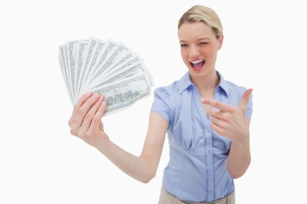 Frau, die geld hält und auf es zeigt