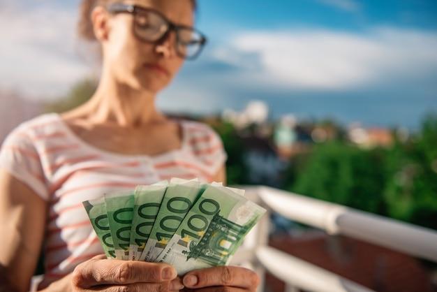 Frau, die geld hält