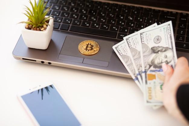 Frau, die geld in der hand nahe einem laptop hält, um btc zu kaufen