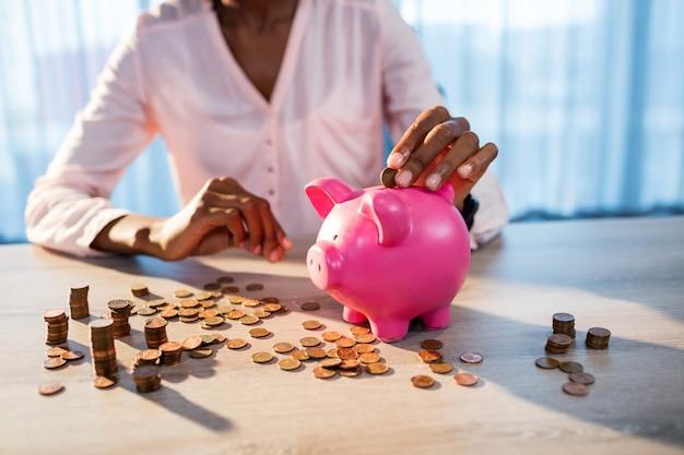 Frau, die geld in ein sparschwein einsetzt