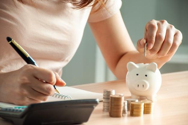 Frau, die geld in ein sparschwein legt