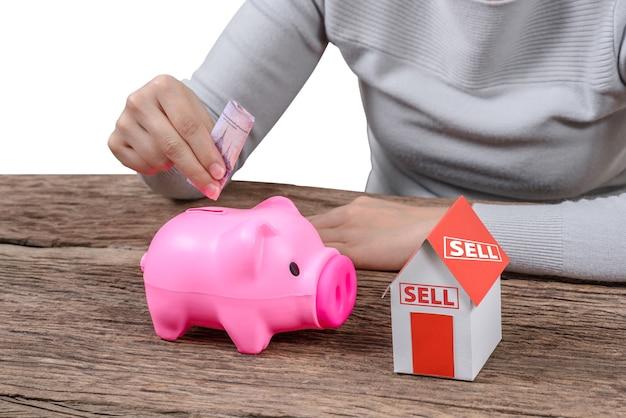 Frau, die geld in ein sparschwein- und modellhaus einfügt