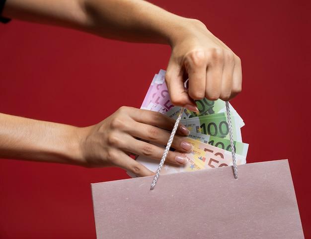 Frau, die geld in eine einkaufstasche einsetzt
