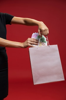 Frau, die geld in ihre einkaufstasche einsetzt