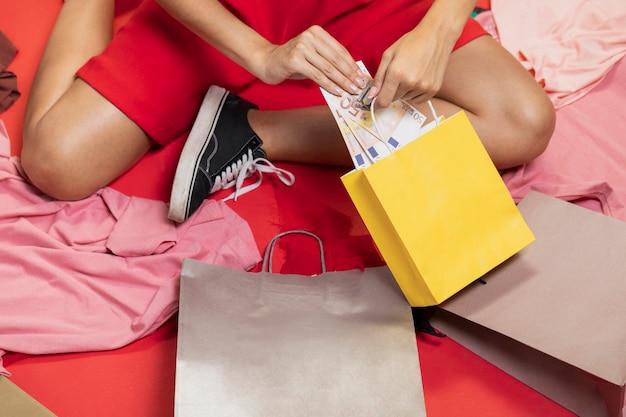 Frau, die geld in ihre einkaufstaschen einsetzt