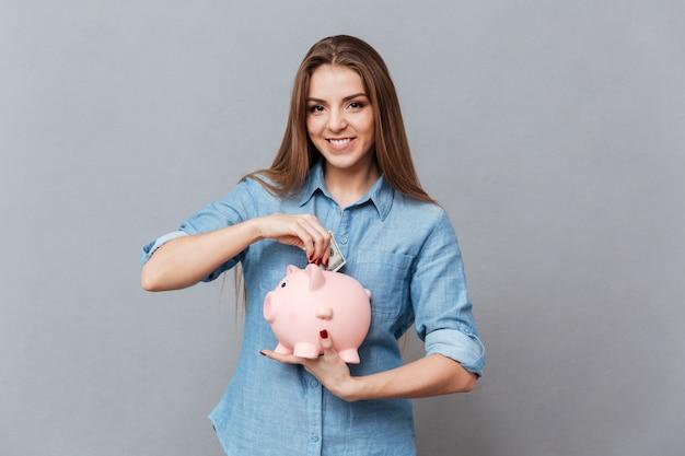 Frau, die geld in sparschwein setzt