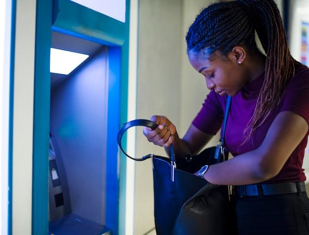 Frau, die geld von einer bargeldmaschine abhebt