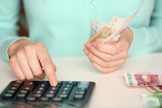 Frau, die geld zählt und am taschenrechner am tisch arbeitet