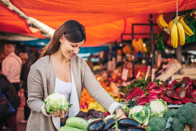 Frau, die gemüse am markt wählt.