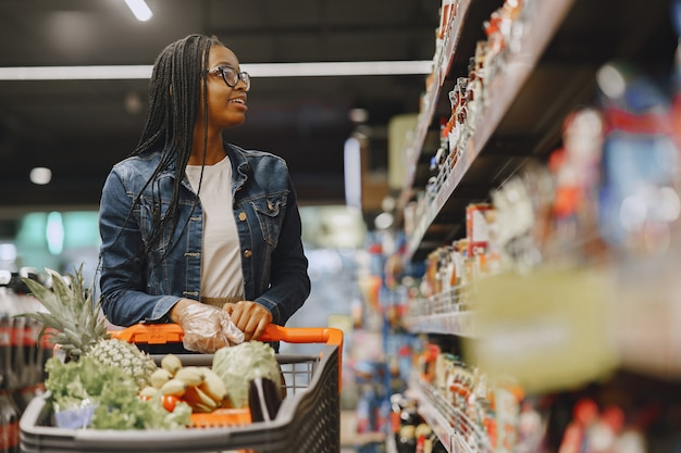 Frau, die gemüse am supermarkt einkauft