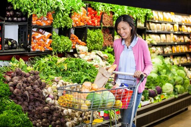 Frau, die gemüse im bio-bereich kauft