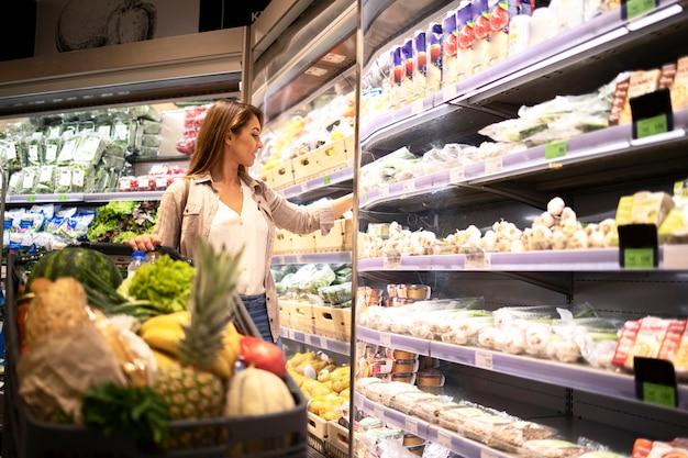 Frau, die gemüse im supermarkt kauft