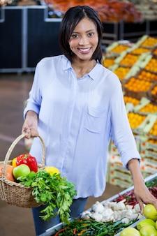 Frau, die gemüse und früchte im bio-bereich kauft