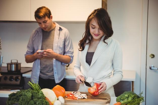 Frau, die gemüse und mann mit handy in der küche hackt