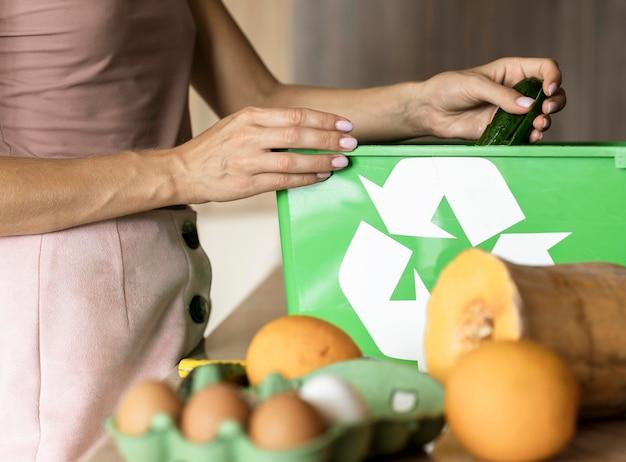 Frau, die gemüsereste recycelt