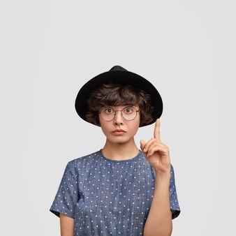 Frau, die gepunktete bluse und großen hut trägt
