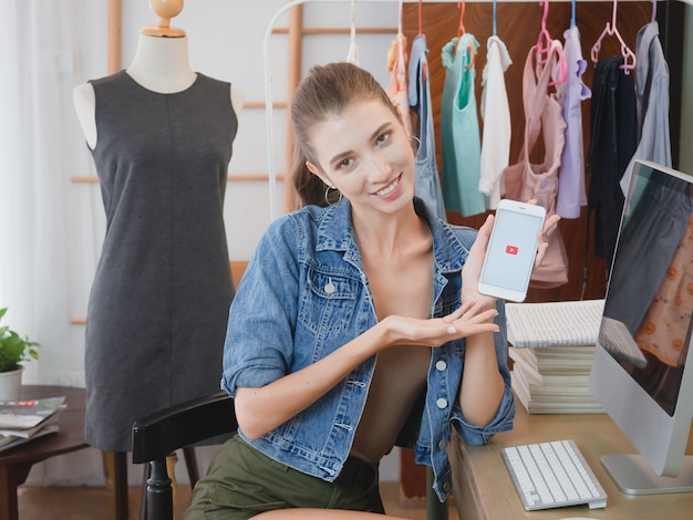 Frau, die geschäft in ihrem haus mit telefon, mädchen verkauft kleidung online mit computer tätigt