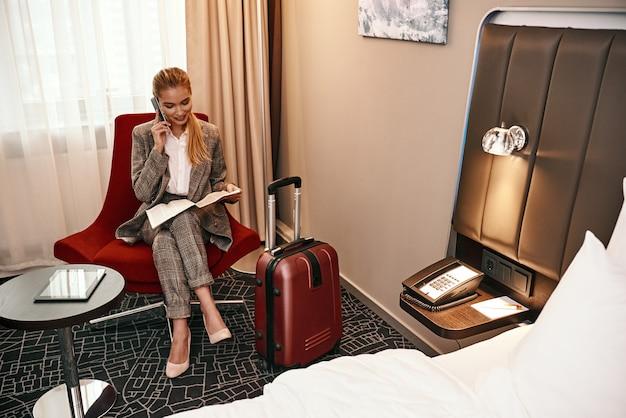 Frau, die geschäftsreise anruft. junge und stilvolle geschäftsfrau mit koffer und smartphone, die auf dem sofa im hotelzimmer sitzt. digitales tablet am tisch