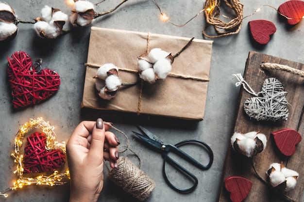 Frau, die geschenk für verpackung zum valentinstag vorbereitet