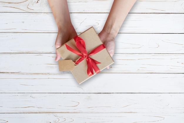 Frau, die geschenkbox auf hölzerner planke hält und in der weißen farbe gemalt