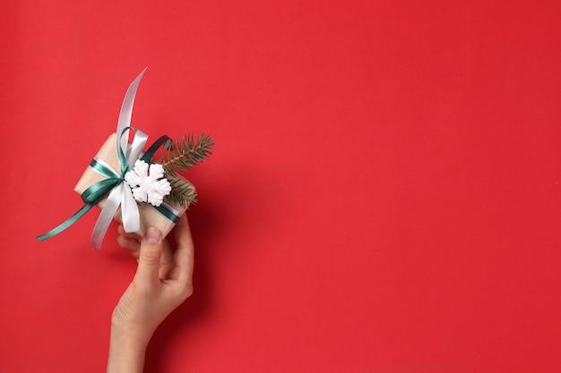 Frau, die geschenkbox des kraftpapiers mit bändern auf rotem hintergrund hält. gruß weihnachtskarte. boxtag. sicht von oben