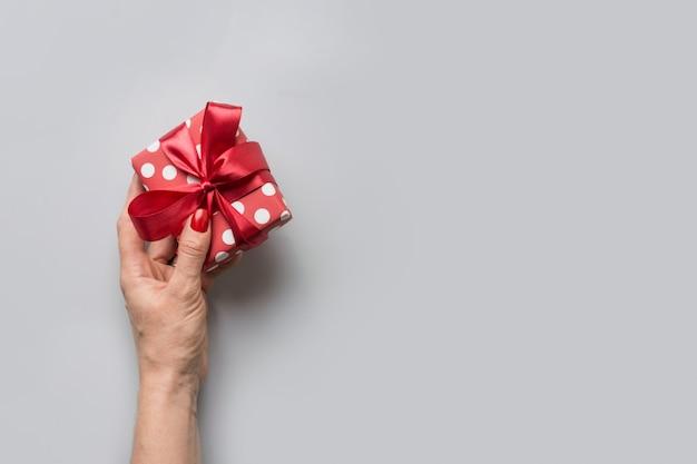 Frau, die geschenkbox mit bogen auf grau hält