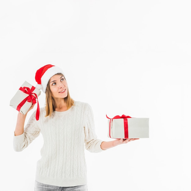 Frau, die geschenkbox nahe ohr hält